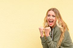 Excited blond woman cheering clenching her fists. Excited blond woman cheering and clenching her fists as she celebrates a personal victory or success over a royalty free stock photo