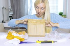 Excited blond woman sitting and opening a box, a parcel, objects on the table are in mess royalty free stock images