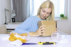 Excited blond woman sitting and opening a box, a parcel, objects on the table are in mess stock photo