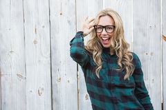 Excited blonde with hand on her glasses posing Stock Photo