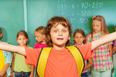 Excited boy with arms apart wears near chalkboard Stock Photos