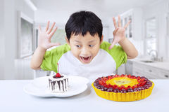 Excited boy eating dessert at home Stock Photo
