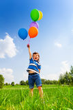 Excited boy with colorful balloons in green park Royalty Free Stock Photo