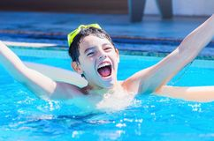 Excited boy enjoying his holidays with a big smile on face insid. E the swimming pool on a summer day. Boy smiling with open arms Royalty Free Stock Photo