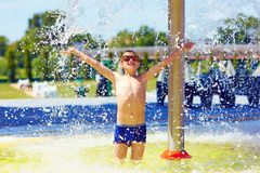 Excited boy enjoying summer under the water flow Stock Photos