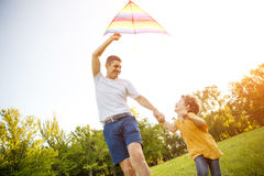 Excited boy with father setting kite Stock Photos