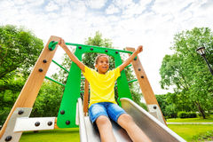 Excited boy with hands up on children chute. On playground in summer Royalty Free Stock Images