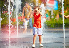 Free Excited Boy Having Fun Between Water Jets, In Fountain. Summer In The City Stock Photo - 75216790