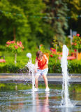Excited boy having fun between water jets, in fountain. Summer in the city Stock Images