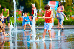 Excited boy having fun between water splashes, in fountain. Summ Royalty Free Stock Photos