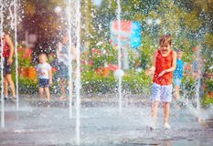 Excited boy having fun between water splashes, in fountain. Summ Stock Photo