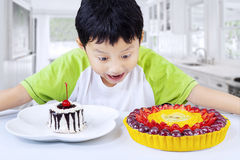 Excited boy looking at desserts at home Stock Photography