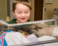Excited boy meets his infant sibling after delivery Stock Photography