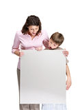 Excited boy and mother holding an empty billboard Stock Images