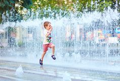 Excited boy running between water flow in city park Royalty Free Stock Images