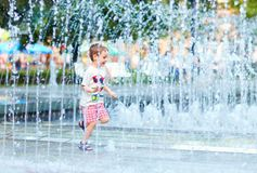 Excited boy running between water flow in city park Stock Photos