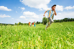 Excited boy runs away from his mates in field. During summer time Royalty Free Stock Image