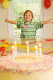 Excited boy (4-6) sitting at end of table at home, arms out, looking at birthday cake in foreground, smiling, front view, portrait Royalty Free Stock Photography