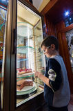 Excited Boy Standing In cake shop Stock Image