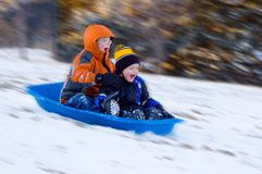 Excited Boys on Sled Ride. Two Excited Boys on a Snow Sled Ride Stock Photography