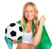 Excited Brazilian team fan. Portrait of happy excited Brazilian football team fan with closed eyes isolated on white background, holding in hand ball and Brazil Royalty Free Stock Photography