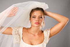 Excited bride earing a veil in studio Royalty Free Stock Photography