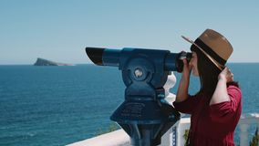 Excited brunette adventures in summer holidays. Cute pretty feminine woman in red dress and straw hat, typical token tourist looks through telescope on stock video footage