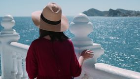 Excited brunette adventures in summer holidays. Young female tourist or adventurer with mirror-less camera explores ancient old white beautiful village. next to stock video footage