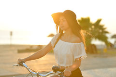 Excited brunette in black floppy hat holding. Portrait of attractive amazed brunette with open mouth wearing black hat and white top having fun riding her Royalty Free Stock Images