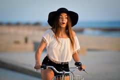 Excited brunette in black floppy hat holding. Portrait of attractive amazed brunette with open mouth wearing black hat and white top. Sexy girl having fun riding Royalty Free Stock Photography