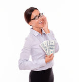 Excited brunette businesswoman holding some money. Excited brunette businesswoman holding money with an impressed gesture of her hand to her face while wearing Stock Image