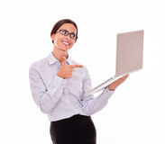 Excited brunette businesswoman with a laptop. Excited brunette businesswoman looking at a laptop very satisfied while pointing at the laptop and wearing her Stock Photography