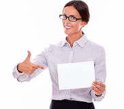 Excited brunette businesswoman with a signboard. Excited brunette businesswoman with glasses, wearing her long hair tied back, and a button down shirt, holding a Royalty Free Stock Image