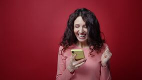 Excited brunette female get good news, message of lottery win on smartphone app start happy dancing