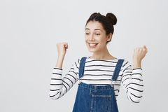 Excited brunette girl with hairbuns in striped top and denim clothes glad to achieve sucess, clenches fists and smiling. In excitement, glad to pass all exams Stock Image