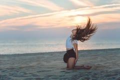Excited brunette girl sitting on sandy beach Stock Image