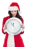 Excited brunette holding a clock Stock Images