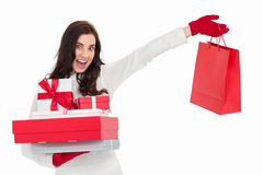 Excited brunette holding gifts and showing shopping bag Royalty Free Stock Images