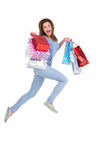 Excited brunette jumping while holding shopping bags Stock Photos