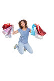 Excited brunette jumping while holding shopping bags Royalty Free Stock Images