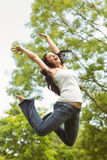 Excited brunette jumping in the park Stock Photo