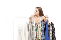 Excited brunette looking at clothes. Young brunette woman looking at clothes with excitement Royalty Free Stock Photos