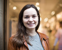 Excited  brunette posing in clothing store and smiling. Excited young european brunette posing in clothing store and smiling Stock Photo