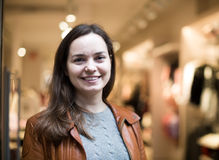Excited  brunette posing in clothing store and smiling. Excited young russian brunette posing in clothing store and smiling Royalty Free Stock Photo