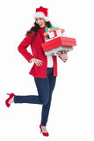 Excited brunette in red coat holding many gifts Royalty Free Stock Image
