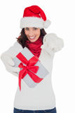 Excited brunette in santa hat giving gift Stock Photos