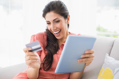 Excited brunette sitting on her sofa using tablet to shop online Stock Images