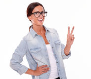 Excited brunette woman showing victory sign. While looking at the camera with a toothy smile and her long hair tied back while wearing a tank top and denim Royalty Free Stock Images