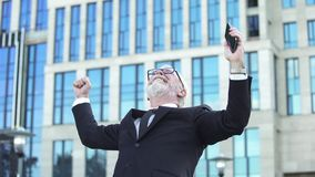 Excited business male in suit showing success sign holding mobile, achievement stock photo
