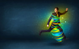 Excited business man jumping with energy colourful lines. Around him Royalty Free Stock Image
